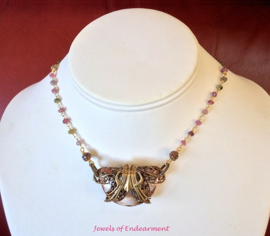 Regency Embellished Necklace  A lovely blush faceted antique glass wrapped in fine filigree is accented by tourmaline rondelles.