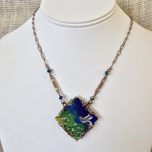 Night Flight Necklace  Deep blues and verdant greens summon a feathered friend to take flight. Brass filigree and fire polished faceted rondelles accent the hand painted centerpiece.