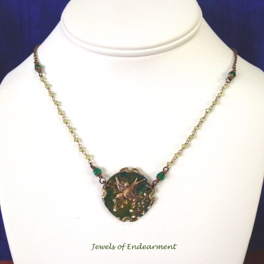 Among the Trees Necklace  Apitite and jade delicately suspend a charming bird winging his way midst greens of all shades.