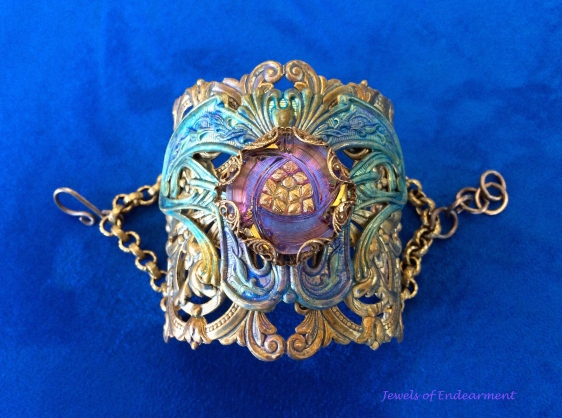 Winged Filigree Nouveau Fan Bracelet This romantic cuff has a vintage look to it with layers of stamped brass painted with shades of amethyst and aqua. Rivets are used to fasten the layers together.