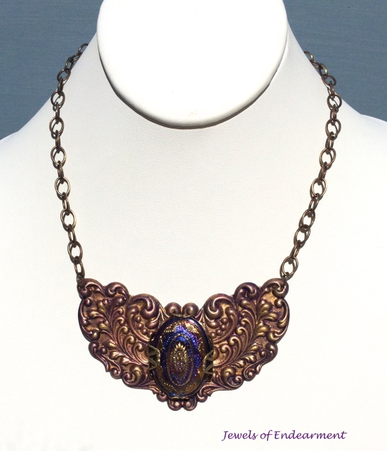 Floral Embellished Necklace Various shades of purples patina provide elegant background for the glass Czech button with cobalt blue and violet metallic hues with gold luster accents.