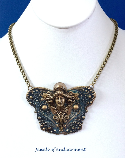 <strong>Masthead Maiden Necklace</strong> Hand-tinted an ultramarine blue using paints and Gilders paste, fastened with micro-screws and epoxy,  this lovely maiden is ready to sail!